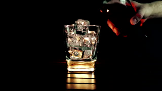 barman pouring whiskey in the glass with ice cubes on wood table and black dark background, focus on ice cubes, whisky relax time - brandy video stock e b–roll