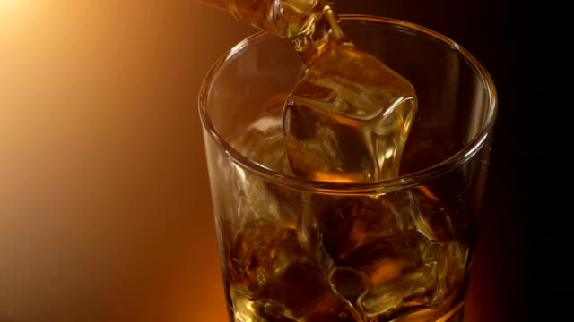 barman pouring whiskey in the glass with reflection , warm evening atmosphere, - whisky video stock e b–roll