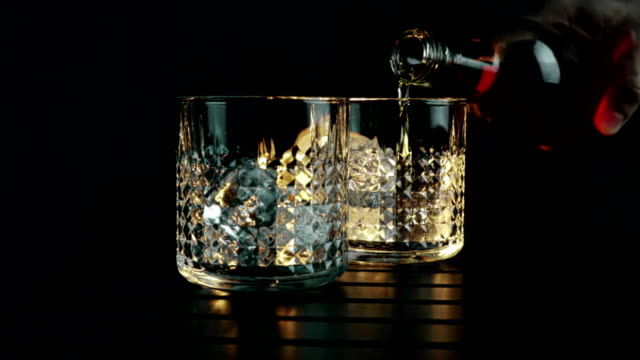 barman pouring whiskey in the two glasses with ice cubes on wood table and black dark background, focus on ice cubes, whisky relax time on warm atmosphere - rum superalcolico video stock e b–roll