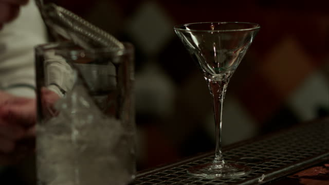 Barman shake ice with martini in glass and pouring it into empty glass video