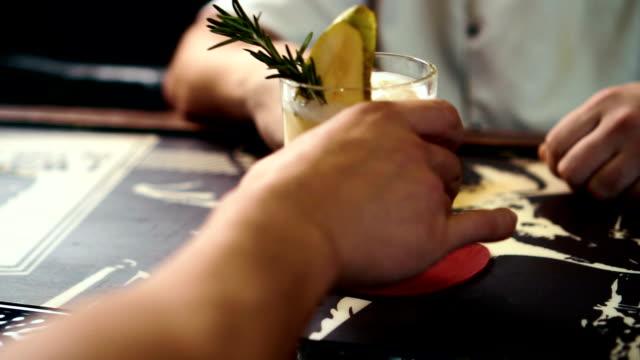 barmer gibt einen leckeren cocktail gelben an dem männlichen kunden in stilvollen bar, nahaufnahme - turngerät mit holm stock-videos und b-roll-filmmaterial