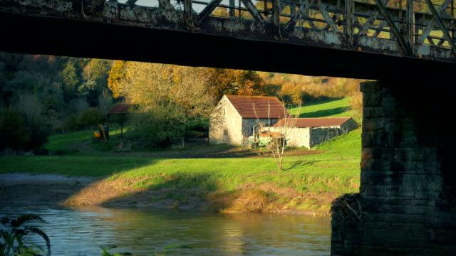 vidéos et rushes de grange encadrée par le vieux pont au coucher du soleil - grange