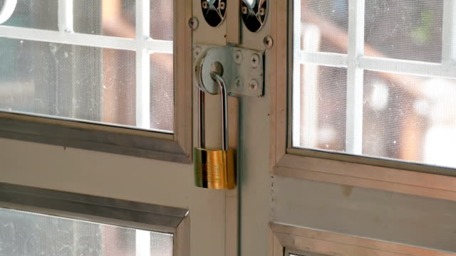 barred gate with a padlock woman's hands barred gate with a padlock padlock stock videos & royalty-free footage