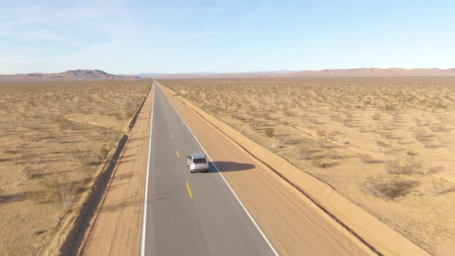 DRONE: Barren landscape surrounds a silver SUV driving down an empty highway. DRONE: Barren landscape surrounds a silver SUV driving down an empty interstate highway connecting the states of Nevada and California. Tourists on road trip cruise across the famous Mojave desert. mojave desert stock videos & royalty-free footage
