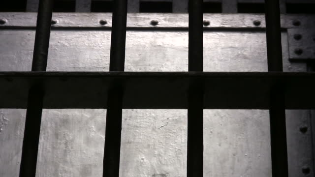 Bars of Steel Zoom out from the bars of a jail cell.  Shot in low natural light to add to the powerful and suspenseful metalic atmosphere. prison bars stock videos & royalty-free footage