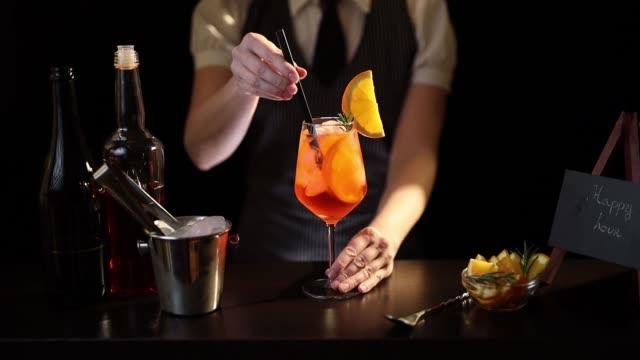 Bartender adding drinking straws into cocktail glass