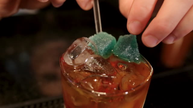 Bartender adding jelly tots to delicious cocktail on bar counter in night club