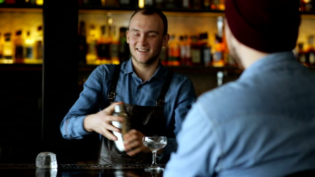Bartender and the customer communicate at the bar during cocktail preparation video