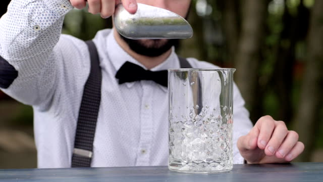 bartender at bar table put clear ice cubes in glass, barman put ice into glass in fresh air, bar worker prepares alcoholic beverage, event Service video