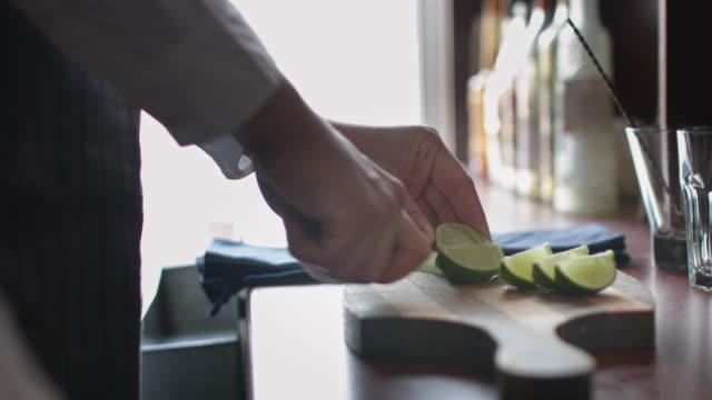 bartender cutting limes - martini video stock e b–roll
