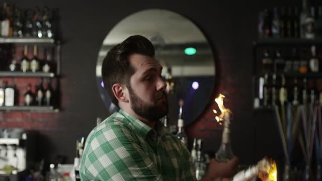 bartender dancing with flaming bottle - трюк стоковые видео и кадры b-roll
