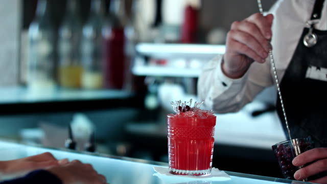 Barman versieren cocktail rode alcoholische cocktail met bessen video