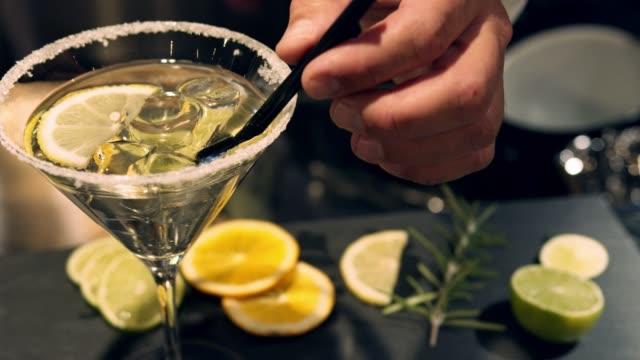 stockvideo's en b-roll-footage met barman hand het toevoegen van rietjes aan martini-close-up - martini