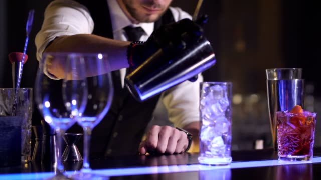 Bartender hand pouring prepared cocktail in glass Closeup of barman gloved hand pouring ready Singapore sling cocktail out from shaker to glass. Stylish bartender during alcoholic drink preparation in nightclub bar counter stock videos & royalty-free footage