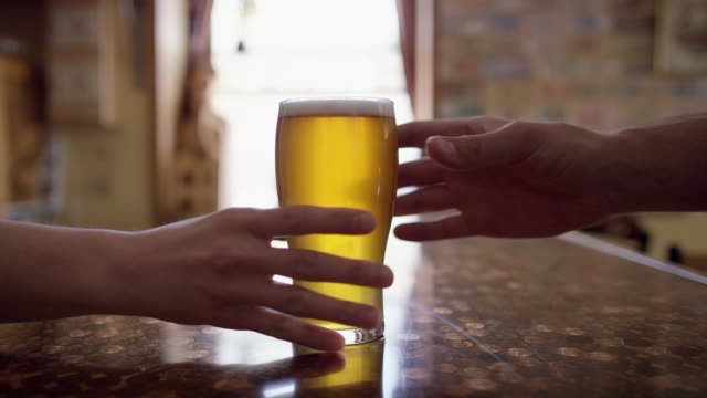 A Bartender Hands a Beer to Someone Across a Bar Counter at a Bar A Caucasian woman hands a frothy beer to a Caucasian man across a bar counter at a bar. wait staff stock videos & royalty-free footage