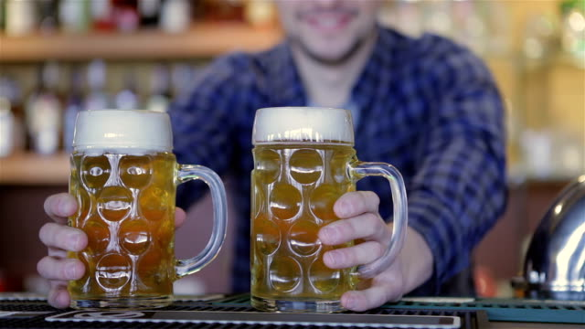 Bartender holding beer glasses and smiling video