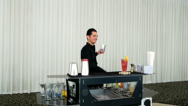 Bartender juggling bottles and shaking cocktail at a mobile bar video