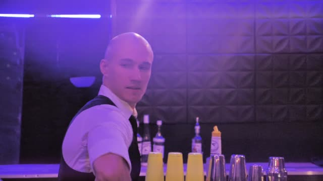 Bartender juggling bottles, the man are showing impressive show in slow motion video