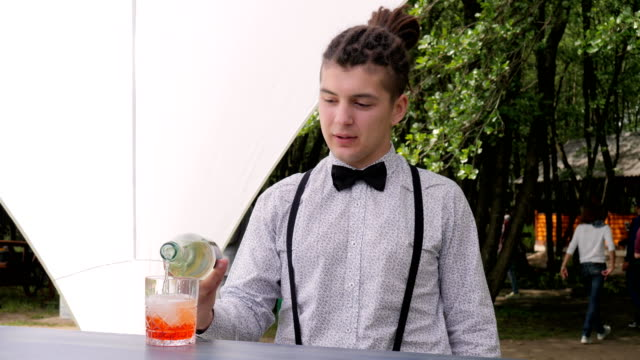 bartender makes mixed drink on background nature, bar worker topped up rom into glass with ice cubes video