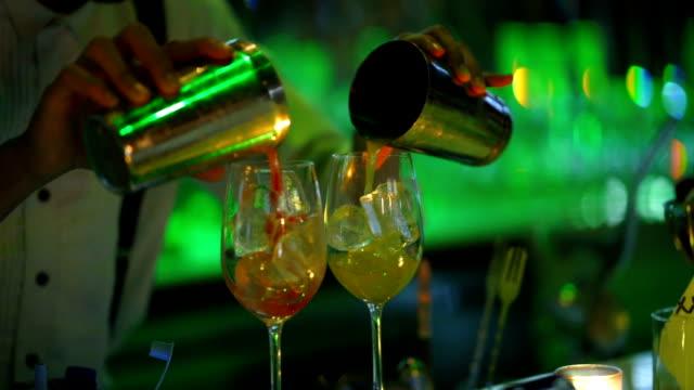 barkodun barda içme bardağı ile karıştırma kokteyl, yakın yukarı barmen el cam içine alkol içecek dökme - bartender stok videoları ve detay görüntü çekimi