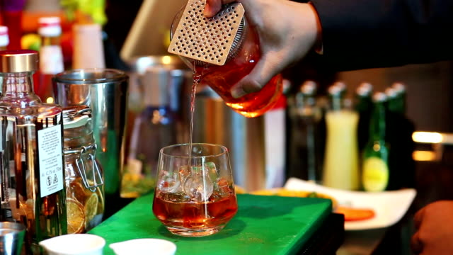 bartender mixing cocktail with drinking glass at bar, close up barman hand pouring a alcohol drinks into glass - rum superalcolico video stock e b–roll