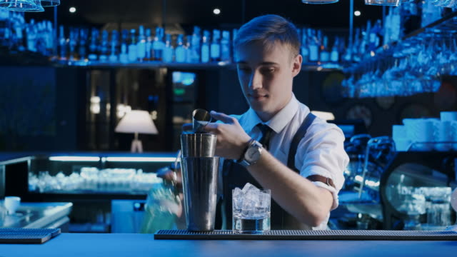 Bartender Mixologist Combining Ingredients and Making Alcoholic Cocktail in Bar. Shot on Red Epic 4k Uhd Camera.