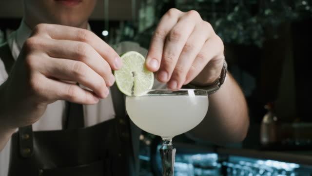 stockvideo's en b-roll-footage met barman mixologist combineert ingrediënten en het maken van alcoholische cocktails in de bar. geschoten op de rode epische 4k uhd-camera. - martini