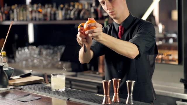 vídeos de stock, filmes e b-roll de barman que descasca uma laranja para o cocktail - descascado