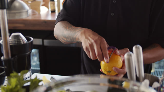Bartender Peeling Orange for Garnish