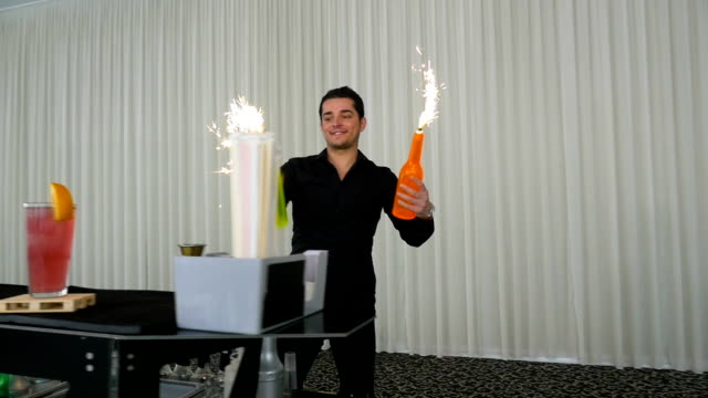 Bartender performing flair bartending with bottles and fireworks in slow motion video