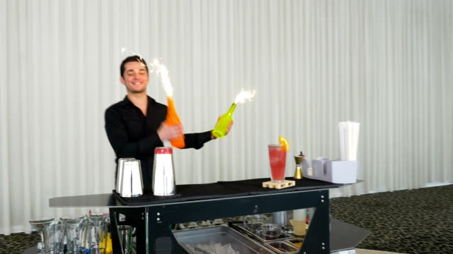 Bartender performing flair bartending with fireworks at a party video