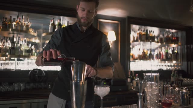 Bartender pouring alcohol in beaker then in glass with ice video