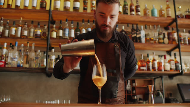 bartender pouring cocktail from shaker to glass - bancone bar video stock e b–roll
