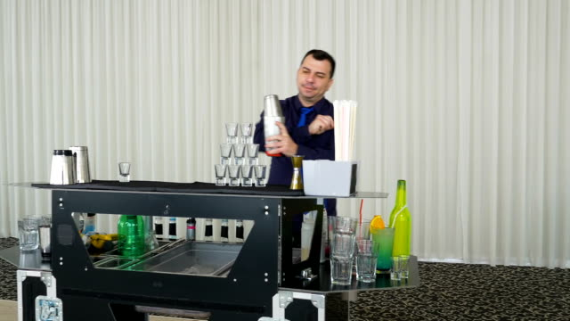 Bartender pouring drinks from shaker into tower shots video