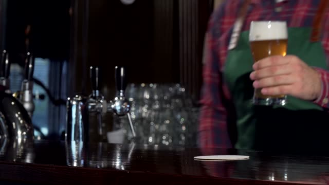 バーテンダーはパブでおいしいビールのグラスを注ぎ、カウンターに置く - 醸造所点の映像素材/bロール