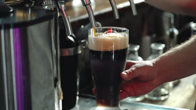 Bartender Pouring Glass of Stout Beer. - video