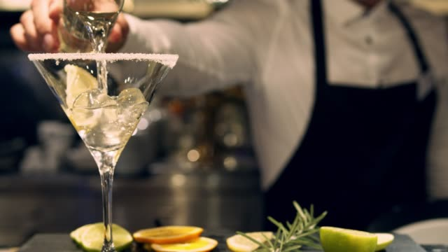 Bartender pouring martini into a glass - slow motion video