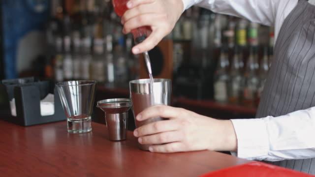 bartender hälla rosa cocktail från shaker - martini bildbanksvideor och videomaterial från bakom kulisserna
