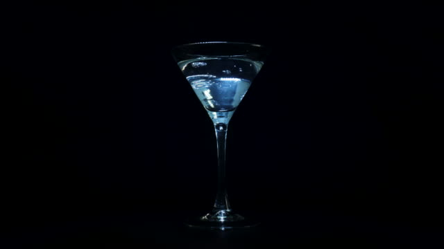 bartender pours a martini coctail into a glass and puts an olive in - martini video stock e b–roll