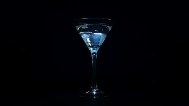 stockvideo's en b-roll-footage met barman giet een martini cocktail in een glas en zet een olijf in - martini