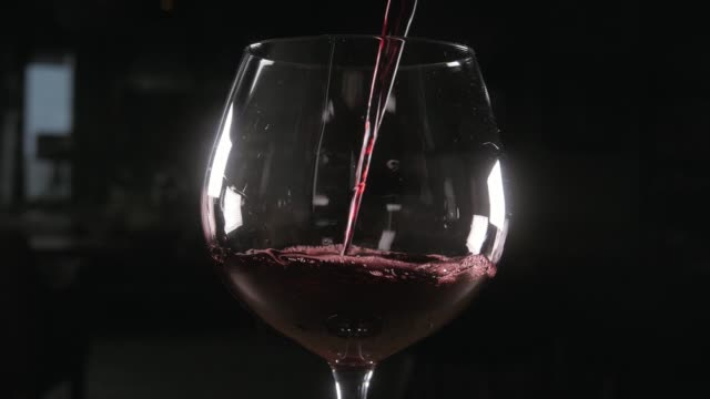 bartender pours red wine in glass from big transparent vessel - decanter video stock e b–roll