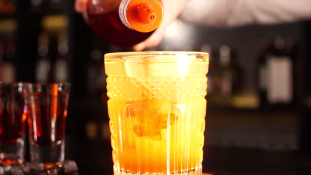 Bartender pours syrup in exotic fruit cocktail Bartender pours syrup in exotic fruit cocktail, Exotic fruit cocktail in glass isolated on blurred restaurant background margarita stock videos & royalty-free footage