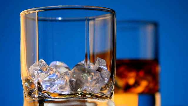 bartender pours whiskey in a glass with pieces of ice and haves gold reflection of light on the edges. - brandy video stock e b–roll