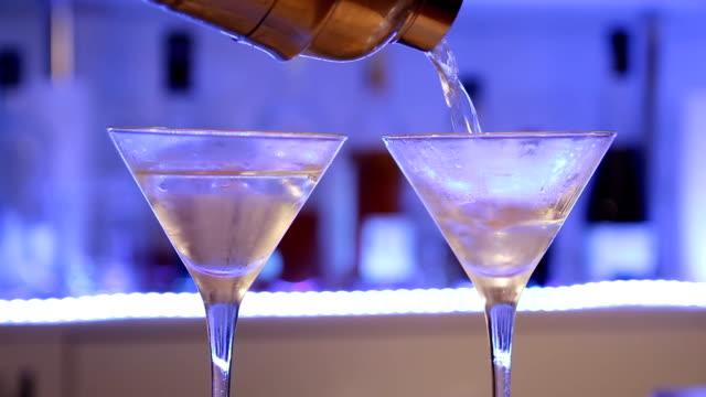 Cocktail alcoólico preparando do barman. Mulher fazendo gim Gibson cocktail com cebolas. - vídeo