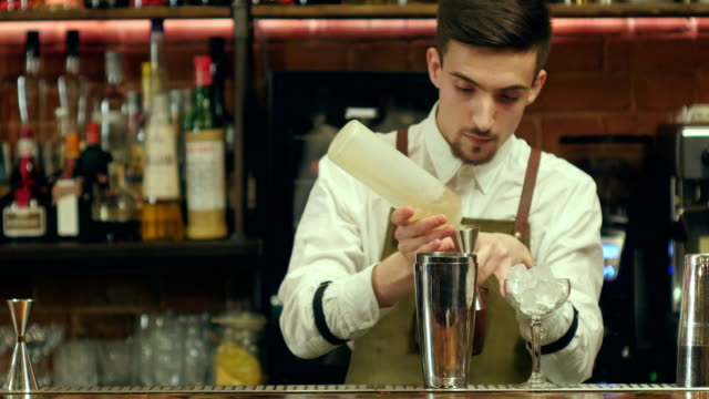 Bartender preparing and pouring non-alcoholic cocktail drink at bar video
