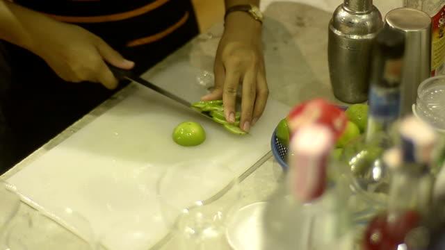 vidéos et rushes de barman préparer à utiliser avec un cocktail au citron vert - un seul homme d'âge mûr