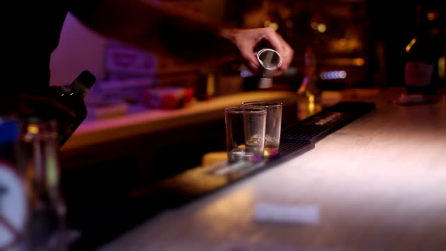 bartender puring a whiskey at nightclub on bar bartender puring two glasses of whiskey for women bar counter stock videos & royalty-free footage