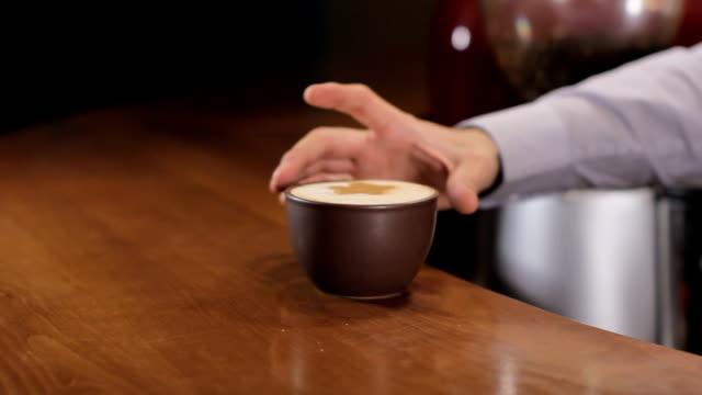 バーテンダーは、木製のバーのカウンターでコーヒー カプチーノを提供しています。女の子がそれを拾ってください。 - ソーサー点の映像素材/bロール