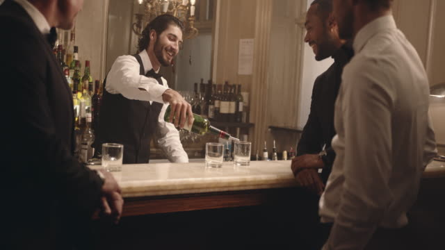 Bartender serving drinks to men at party Male bartender serving drinks to group of men at party. Barman serving alcohol to guest at a nightclub. bartender stock videos & royalty-free footage
