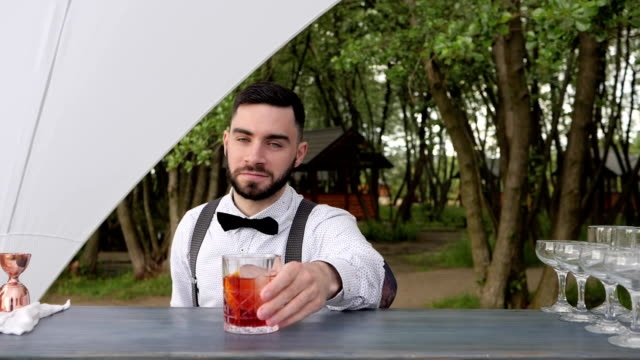 bartender shows gesture of approval, barkeeper thumb up, smiling barman serves whiskey with ice on bar counter, summer restaurant video